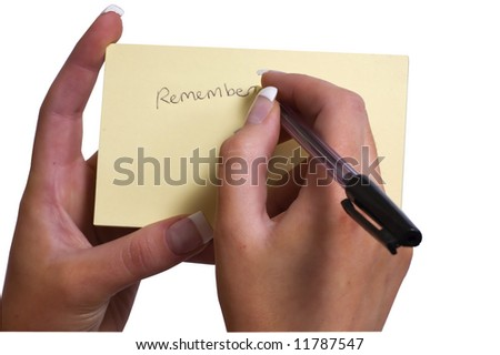 Female Hand writing Remember on Sticky note