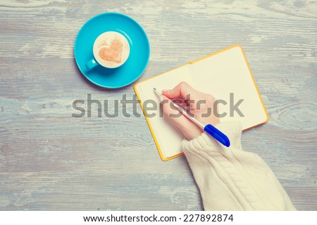 Female hand writing something in notebook near cup of coffee. - stock photo