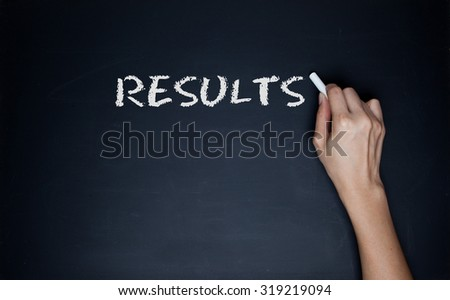 female hand writing the word Results on a blackboard in white text with a stick of chalk - stock photo