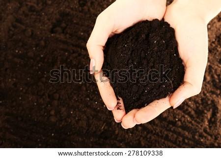Female handful of soil, closeup - stock photo