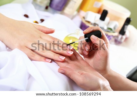 Female hands and manicure related objects in spa salon - stock photo
