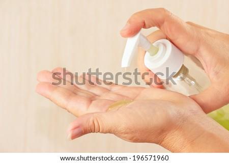 Female hands applying liquid soap close up - stock photo