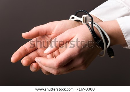 female hands are tied up with computer cables - stock photo