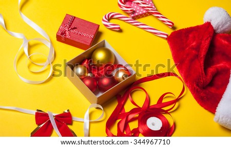 Female hands are wrapping a christmas gift on yellow background - stock photo