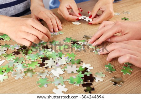 Female hands assembling puzzle on wooden table, closeup - stock photo
