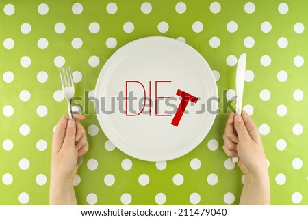 Female hands at dinner table holding fork and a knife above plate as dieting concept. Word Diet becoming Die referring to health issues that diet mistakes can cause. - stock photo