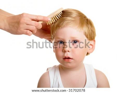 Female hands brush the little boy - stock photo