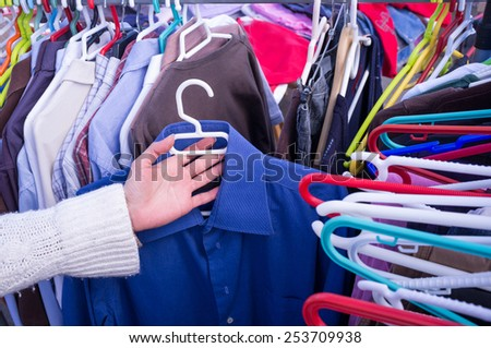 Female hands choosing clothes on a jumble sale market stall - stock photo