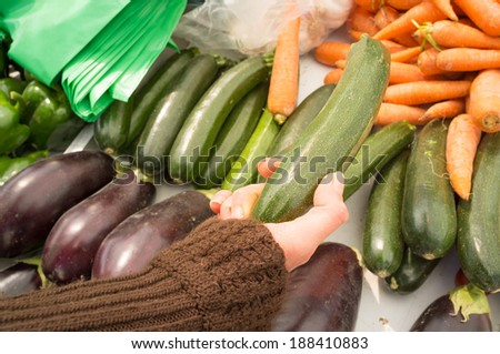 Female hands choosing vegetables on a street market stall