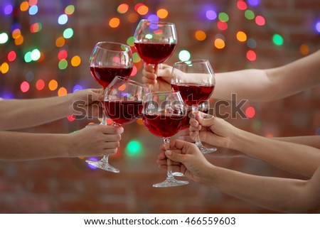 Female hands clinking glases with red wine on bokeh background