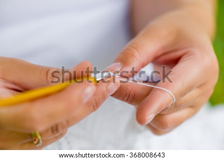 female hands close-up with crochet hooks and cotton thread