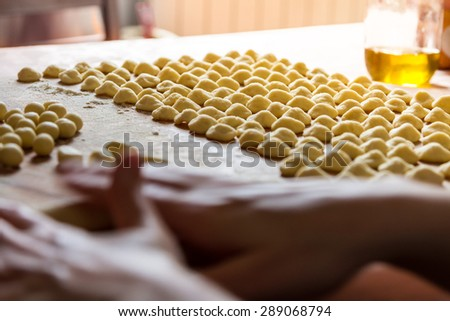Female hands cooking fresh Italian hand made pasta, Orecchiette.  Sun beam coming from the window on the background. Selective focus on the rows of pasta.