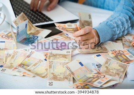 Female hands counting money near laptop at the desk