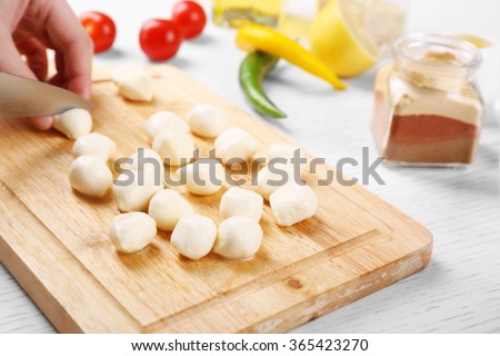 Female hands cutting mozzarella cheese for salad, at kitchen - stock photo