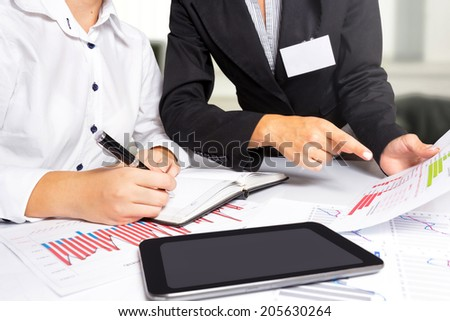 Female hands doing research at office desk, during business meeting.  - stock photo