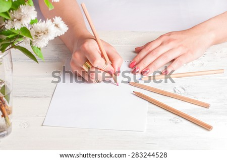 Female hands drawing on white wood background - stock photo