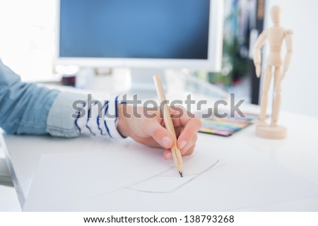 Female hands drawing with pencil on paper on her desk - stock photo