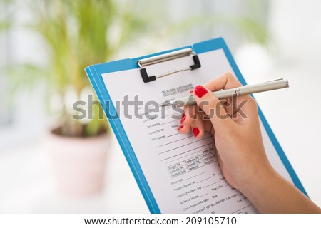 Female hands filling car accident questionnaire - stock photo