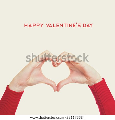 Female hands gesturing heart. Happy Valentine's Day text. Square format, instagram look filter, matte finish.