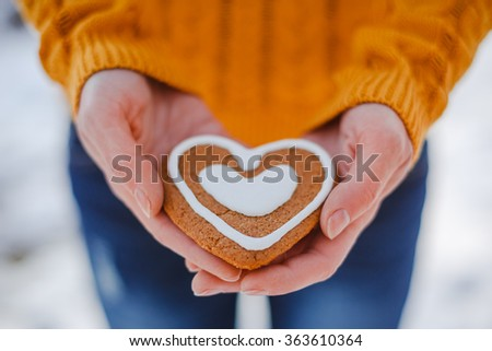 Female hands giving heart shape cookie