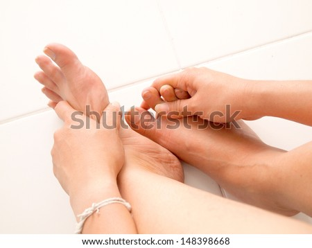 Female hands giving massage to bare foot - stock photo