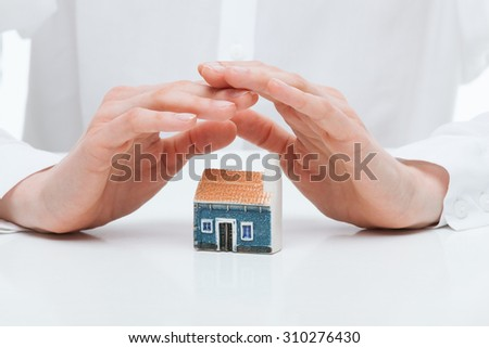 Female hands guards a toy house, white background - stock photo