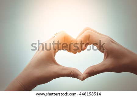 Female hands heart shape on sky. Happy love and freedom concept. Vintage tone color style.