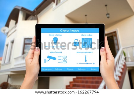 Female hands hold a tablet computer with system clever house on a screen on the background of the house - stock photo