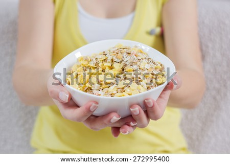 Female Hands Hold Bowl with Cereal Muesli for breakfast. - stock photo