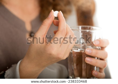 Female hands hold one pill and glass of water close-up - stock photo