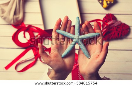female hands holding a blue star to wrap and present it to someone