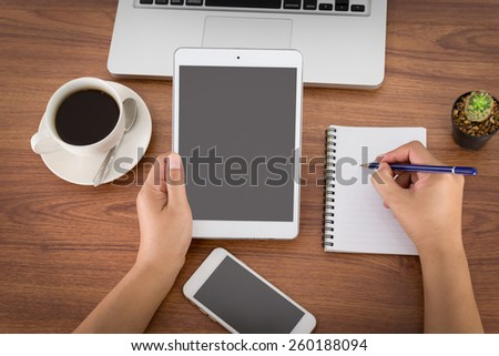 female hands holding a computer tablet on the table in the office - stock photo