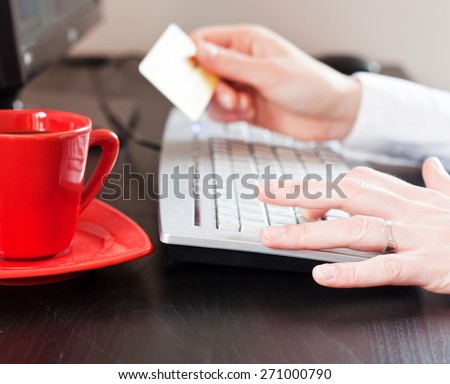 female hands holding a credit card over the desk in the office - stock photo