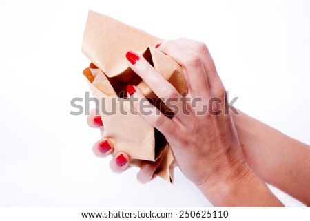 Female hands holding a crumpled paper, white background - stock photo
