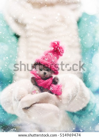 Female hands holding a cute teddy bear. Woman hands in white mittens showing a teddy bear gift dresses in knitted hat and scarf. Cute Christmas present. Winter holidays concept. Snowfall.