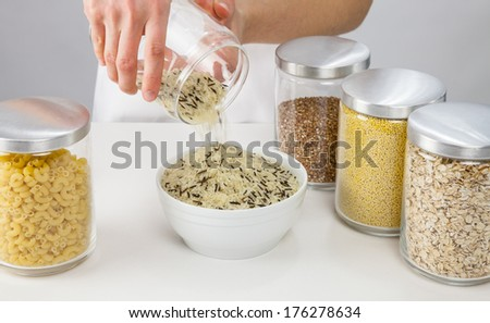Female hands holding a pot with raw rice, grey background - stock photo