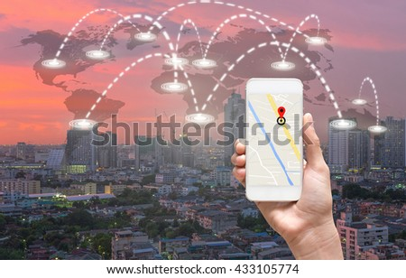 female hands holding a smart phone showing part of navigator map over screen on connection line over the world map with cityscape, Navigation concept,Elements of this image furnished by NASA - stock photo