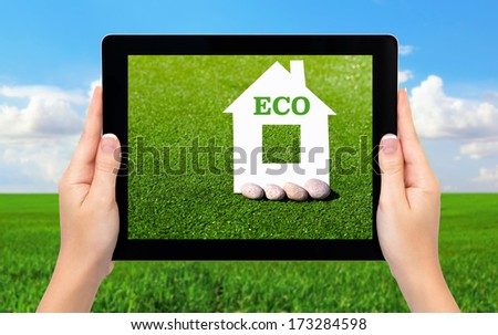 female hands holding a tablet computer with a house and an inscription on eco background of green grass and blue sky - stock photo