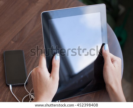 Female hands holding a tablet. Phone and headphones lying next