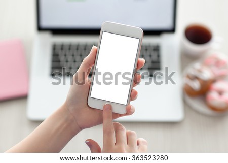 female hands holding a white phone with isolated screen on a table with a laptop - stock photo