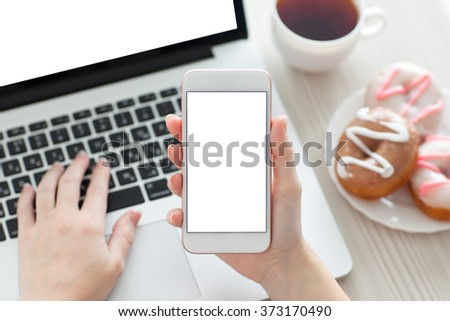 female hands holding a white phone with isolated screen on a table with laptop - stock photo