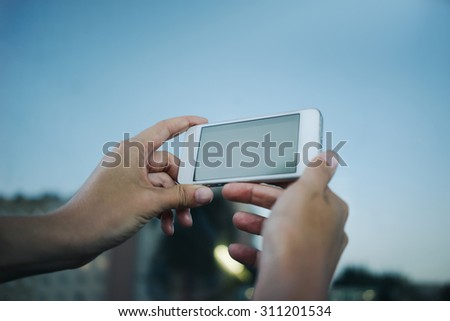 Female hands holding cell phone with copy space screen on the background of afternoon sky, woman photographing outdoors view with digital phone camera - stock photo