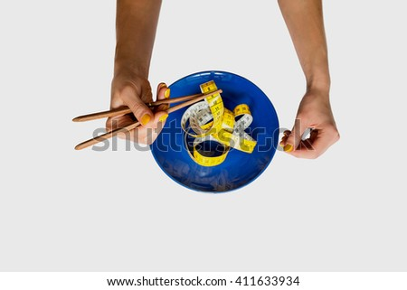 Female hands holding  chinese chopsticks and plate with measure tape isolated on white background - stock photo