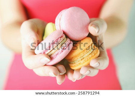 Female hands holding colorful french macaroons - stock photo