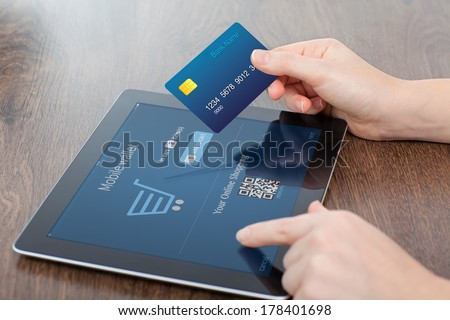 female hands holding credit card and a computer tablet on the table in the office and making a purchase onlain  - stock photo
