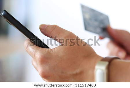 Female hands holding credit card and making online purchase using mobile phone. Shopping, consumerism, delivery or internet banking concept. Anti-fraud and financial security concept - stock photo