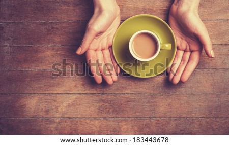 Female hands holding cup of coffee. - stock photo