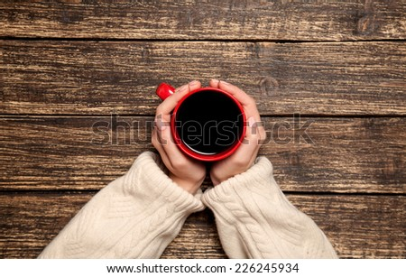 Female hands holding cup of coffee on wooden table. - stock photo