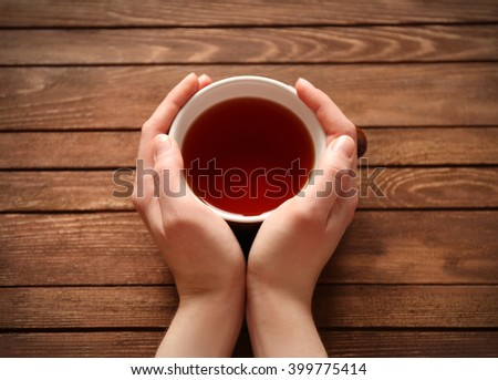 Female hands holding cup of tea on wooden background - stock photo