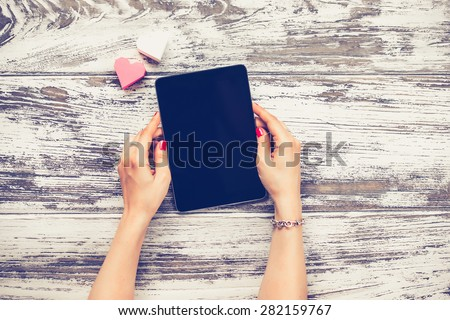 female hands holding electronic tablet old wooden table top view toned image awesome office table top view shutterstock id